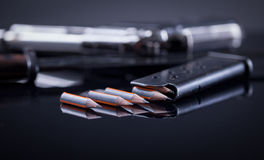 War against terrorism, the concept of freedom of speech and medi. Magazine knife, pen in the form of bullet and blurred gun in the background Royalty Free Stock Images