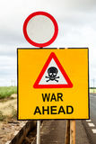 War ahead II. Social concept with a yellow traffic sign and a red warning triangle with a skull and the message war ahead beside the road royalty free stock photography