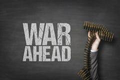 War ahead text on blackboard with businessman hand holding ammunition. War ahead text on black blackboard with businessman hand holding ammunition stock photo