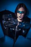 War, Brunette in black latex costume with pistol over broken pap Stock Image