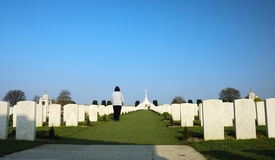 War cemetery. A solitary figure walks up between rows and rows of white headstones in a cemetery filled with graves from the First World War Stock Image