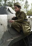 Boy on the war. Child schoolboy on a tank. The boy in the form of a soldier during the Second world war of 1941-1945. stock photos