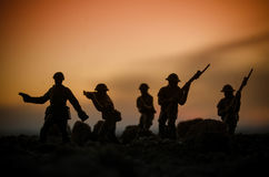 War Concept. Military silhouettes fighting scene on war fog sky background, World War Soldiers Silhouettes Below Cloudy Skyline At Stock Photo