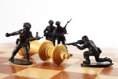 War concept. Toy soldiers kill chess King. Death of king. Royalty Free Stock Image