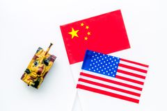 War, confrontation concept. China, USA. Tanks toy near chinese and american flag on white background top view.  stock photography