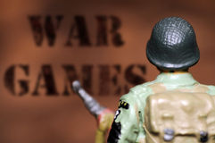 War games. Toy soldier looking towards  war games background Stock Photography