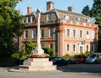 A war memorial landmark in front of a stately home in dedham wit. H some parked cars in summer light close up; UK stock image