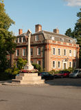 A war memorial landmark in front of a stately home in dedham wit. H some parked cars in summer light; UK stock photo