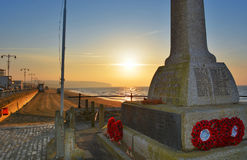 War Memorial and Red Poppy Wreaths at Sunrise. Sunrise over Sandown Bay on the Isle of Wight, UK provides a poignant backdrop to the war memorial at the beach Royalty Free Stock Photo