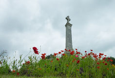 War memorial with wild poppies. Memorial to soldiers of the first world war, surrounded by wild poppy flowers blowing in the wind Royalty Free Stock Images
