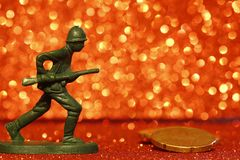 War and money. Toy soldier on a red sparkling background and coins stock photography