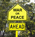 War Or Peace Ahead Sign. Yellow sign with black letters of War Or Peace Ahead with trees in the background royalty free stock image