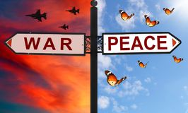 War or peace choice on a signpost with arrows in two opposite directions. Red dramatic sunset sky with flying jets against calm bl. Ue sky with butterflies royalty free stock photo