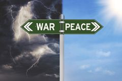 War or peace decision on a green signpost. With a thunderstorm and blue sky on the background Stock Images