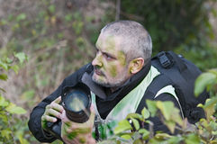 War photographer camouflaged in the vegetation Stock Photo