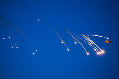 War plane dropping flares. In evasion maneuver royalty free stock photography