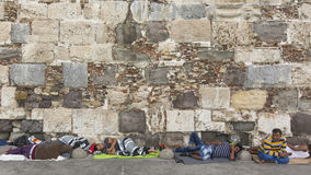 War refugee sleeping on the ground along the stone wall. Royalty Free Stock Image