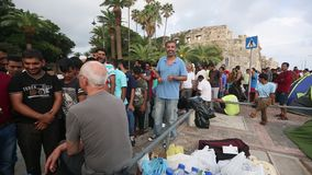 War refugees near tents on the sea waterfront. More than half are migrants from Syria