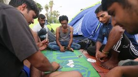 War refugees playing cards near the tents. More than half are migrants from Syria stock video