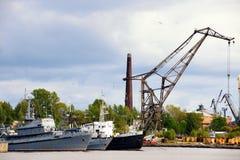 War ship and tug boat in port near crane Stock Photos