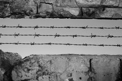War symbol. Stone wall with barbed wire Royalty Free Stock Photos