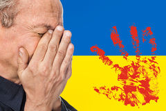 The war in Ukraine. Elderly man covered his face against of Ukrainian flag with bloody handprints Royalty Free Stock Photos
