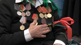 War veteran with hand over heart and awards. Orders and medals on female veteran chest. Celebration of Victory Day royalty free stock image
