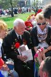 A war veteran holds flowers. Stock Photos