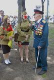 War veteran man portrait. He receives flowers from young women Royalty Free Stock Image