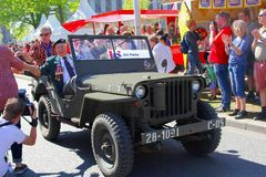 May 2018, War veteran old timer military jeep Liberation Day, Netherlands. Elderly Canadian war veteran is driving in military jeep and making city tour while stock photos