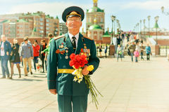 War veteran. Photo veteran standing holding flowers in the square Stock Images