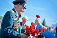 War Veteran. Photo veteran of World War II, which the child gives flowers royalty free stock image