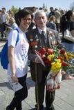 War veteran poses for photos with a young woman. Royalty Free Stock Photos