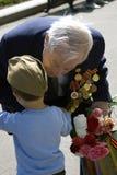 War veteran receives flowers from a boy. Stock Photo