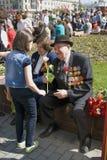 War veteran receives flowers from a girl. Stock Photos