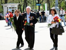 A war veteran walks with flowers Royalty Free Stock Images