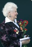 War veteran woman portrait. She holds flowers. Royalty Free Stock Images