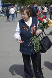 War veteran woman portrait. She holds flowers. Royalty Free Stock Photos