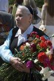 War veteran woman portrait. She holds flowers. Stock Photos