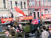 War veterans drive in cars, red Soviet flag waves above. Royalty Free Stock Photos