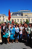 War veterans sing war songs. Soviet army red flag waves above people. Stock Photo