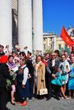 War veterans sing war songs. Soviet army red flag waves above people. Royalty Free Stock Image