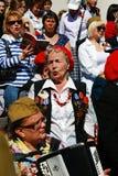 War veterans sing war songs. A woman plays accordeon. Stock Photo