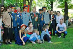 War veterans and their families pose for photos. MOSCOW - MAY 09, 2016: War veterans and their families pose for photos.  Victory Day celebration in Gorky park Royalty Free Stock Photography
