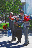 War veterans walk with flowers buds in Gorky park. Stock Photo