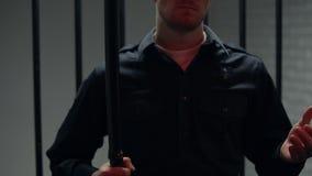 Warden стоя около клетки с дубинкой, красными светами моргая, применением суровых мер протеста видеоматериал