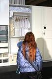 Wardrobe. Girl considers wardrobe in shop Stock Photo