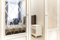 Wardrobe in the bedroom with a mirror smooth and with a bevel. Interior stock photography