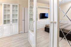 Wardrobe in the bedroom with a mirror smooth and with a bevel. Interior Stock Photo
