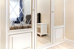 Wardrobe in the bedroom with a mirror smooth and with a bevel. Interior royalty free stock photography